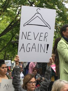 Abortion Ban Protester holding sign with a wire hanger, saying never again.